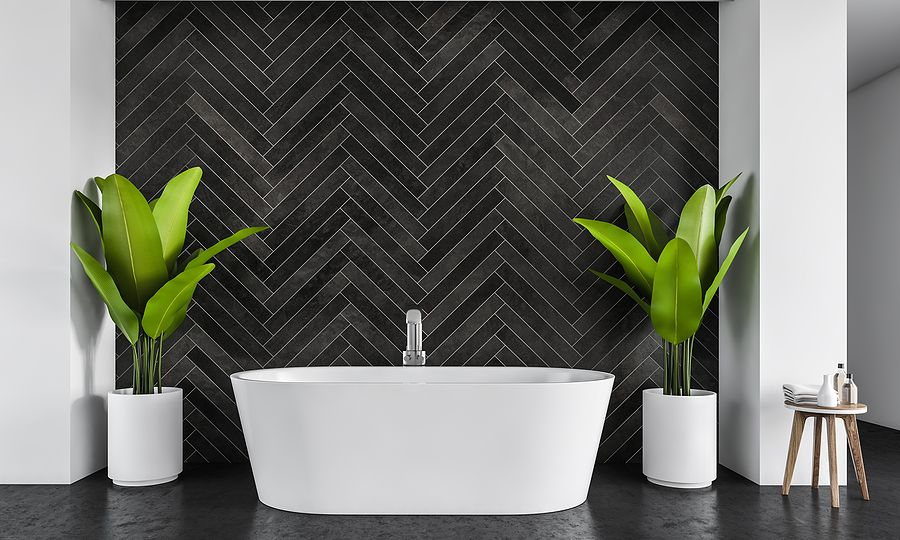 White Bath Against Black Tile Wall In A Big Bathroom With Plants